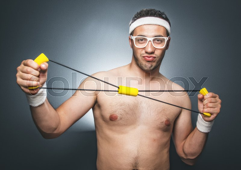 Funny man exercising over dark gray background. Nerd guy with eyeglasses holding expander. Close up of silly young man doing aerobics. Studio shot, stock photo