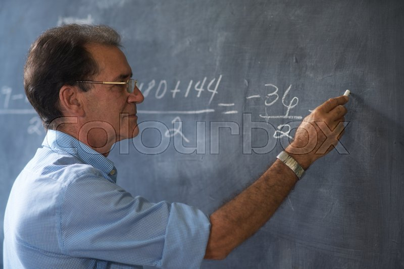 People and education. Teacher writing on math equation on blackboard during lesson, stock photo