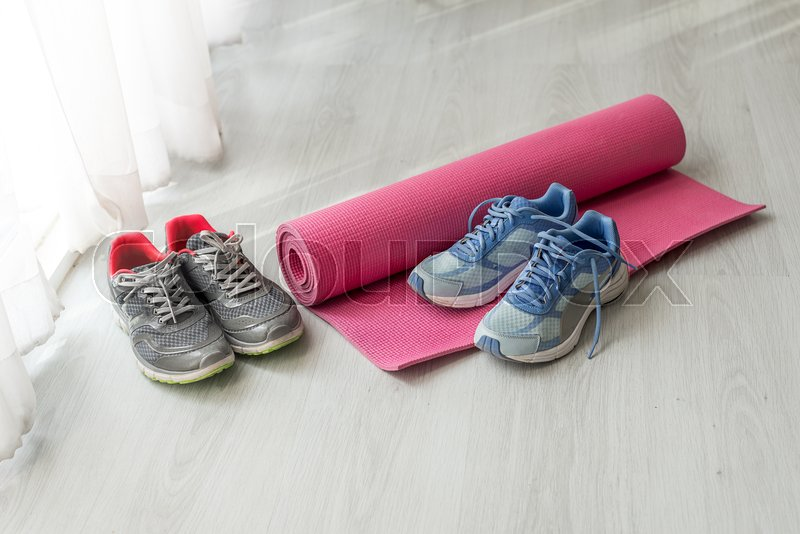 Dirty sport shoes on floor with yoga mat at home. Lifestyle concept. Copy space, stock photo