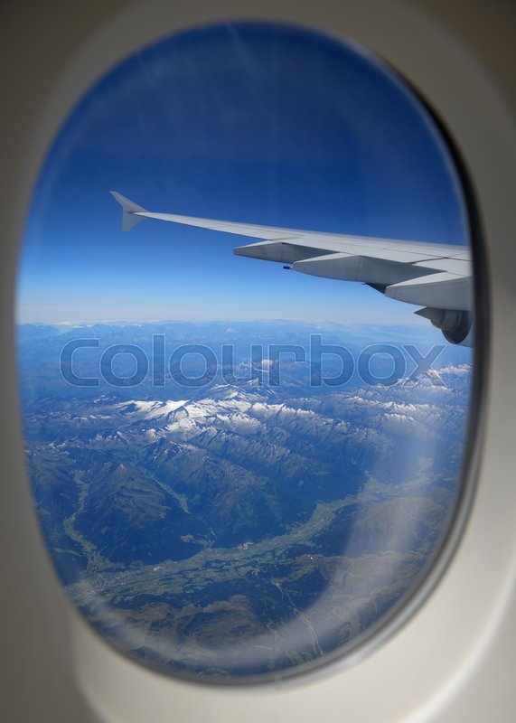 Looking through window, airplane wing and terrain with a nice blue sky, stock photo