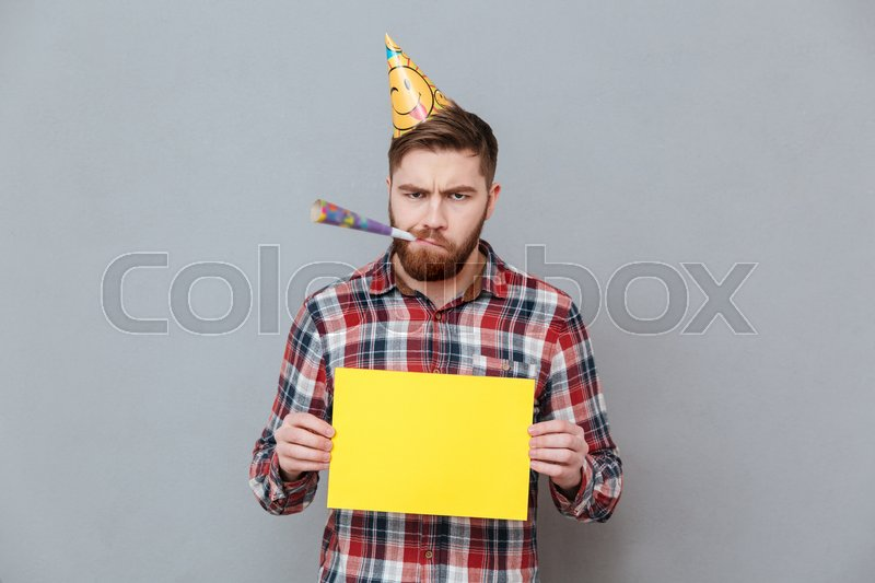 Photo of confused sad young bearded birthday man holding copyspace board standing over grey background, stock photo