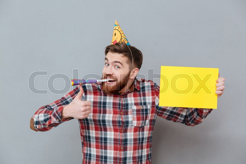 Photo of cheerful young bearded birthday man holding copyspace board make thumbs up gesture standing over grey background, stock photo