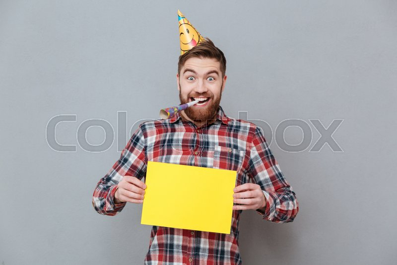 Picture of happy young bearded birthday man holding copyspace board standing over grey background, stock photo