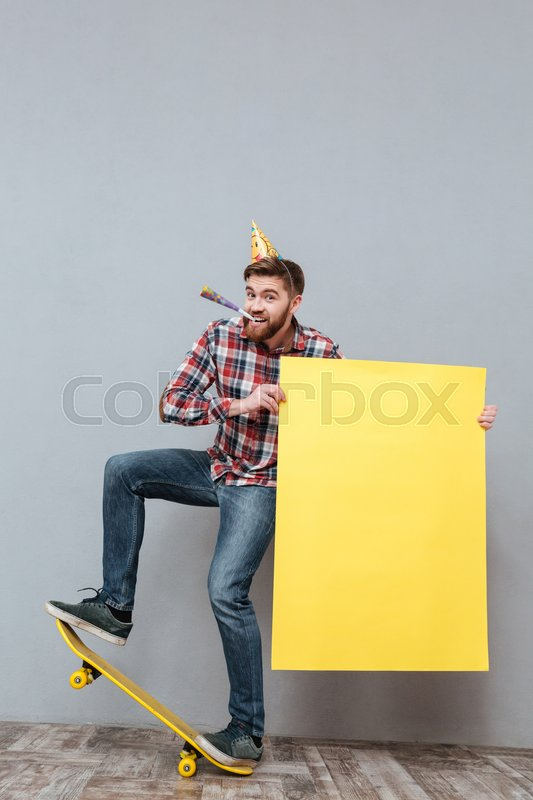 Photo of handsome young bearded birthday man on skateboard holding copyspace board standing over grey background, stock photo