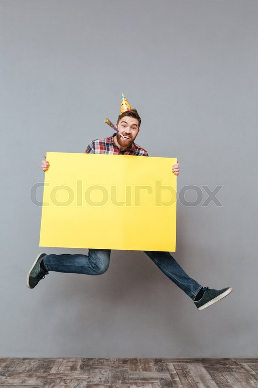 Picture of happy young bearded birthday man holding copyspace board jumping over grey background, stock photo