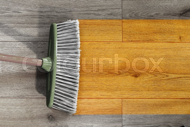Sweeping Away The Dust On Wooden Floor With A Broom Stock Photo
