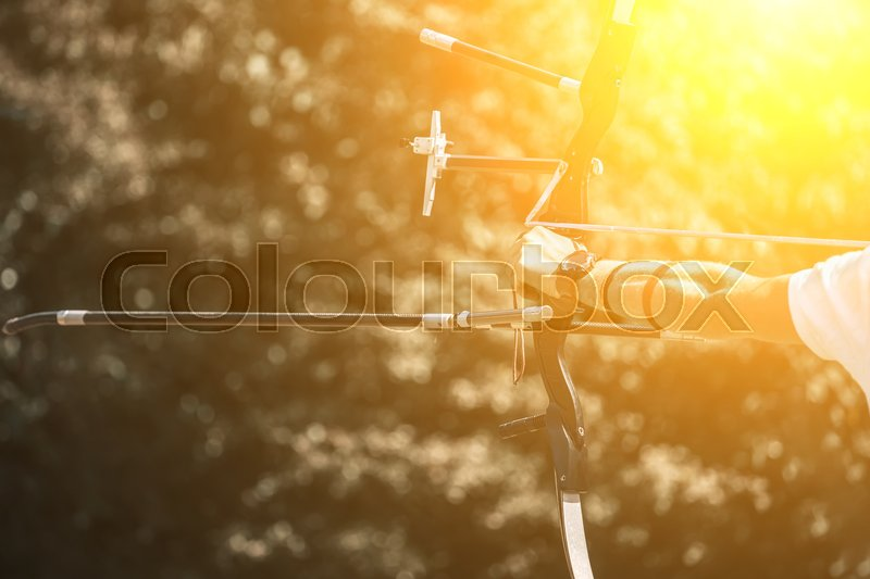Athlete aiming at a target and shoots an arrow. Archery, stock photo