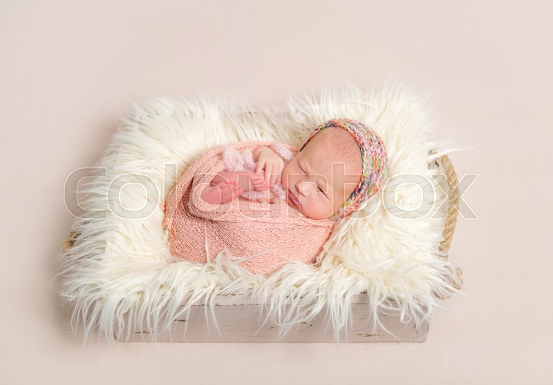 cbf35ec4ff6 Tiny baby girl in a colorful knitted ...