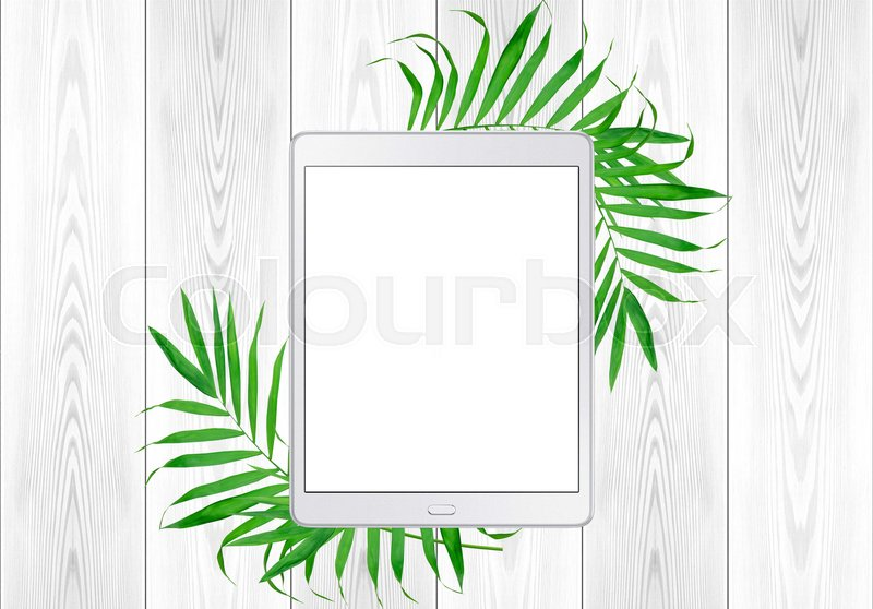 Tablet pc in green fern leaves frame on white wood table. Top View, stock photo