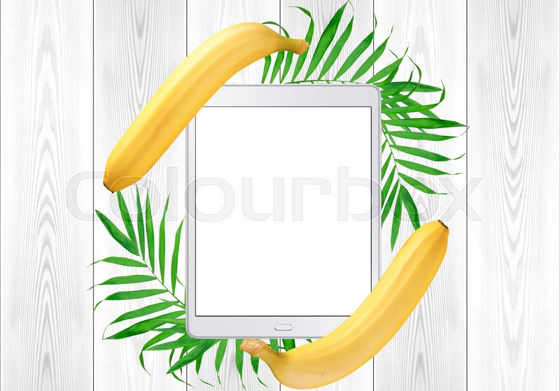 Tablet pc in green fern leaves and banana frame on white wood table. Top View, stock photo