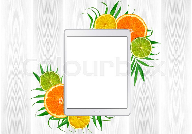 Tablet pc in green fern leaves and citrus fruits; orange, lime; lemon frame on white wood table. Top View, stock photo
