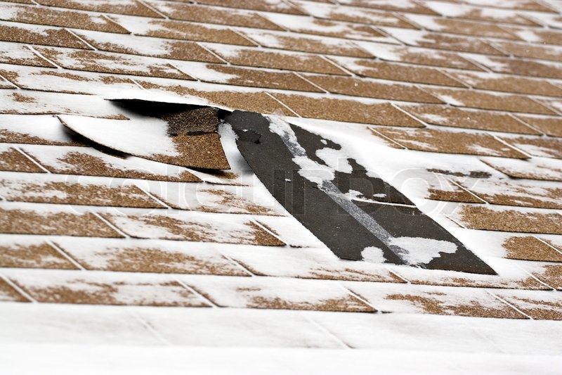 Damaged Roof Shingles Blown Off A Home From A Windy Winter