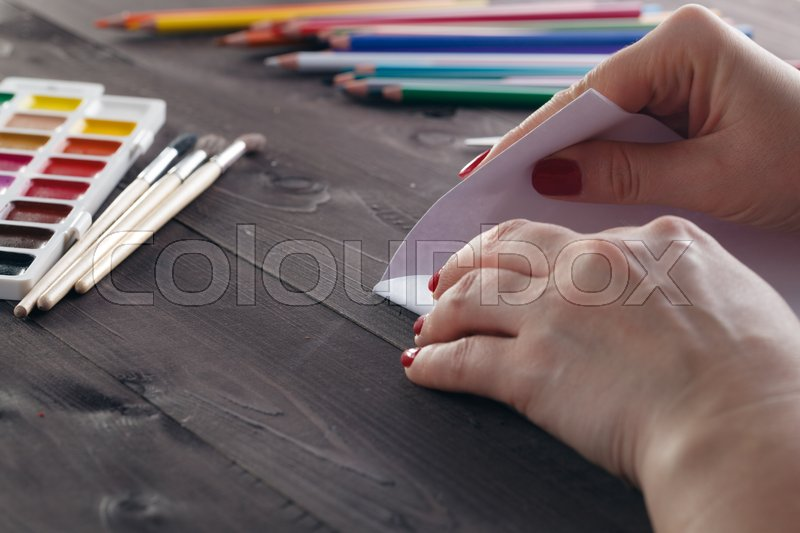 Woman fold sheet of paper while do origami, stock photo