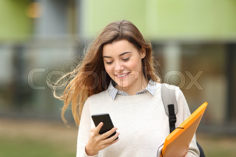 Single student walking and reading mobile phone messages with a university building in the background, stock photo