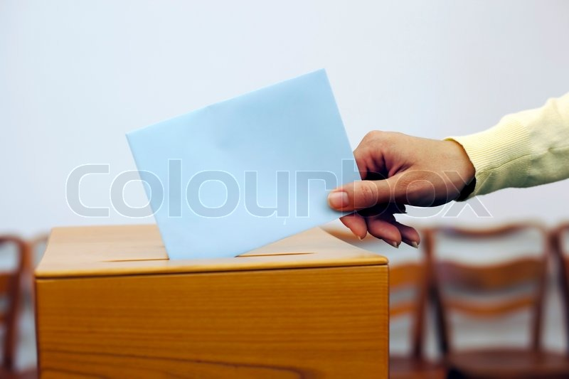 Stock image of 'A young woman with a voter in the voting booth Voting in a democracy'