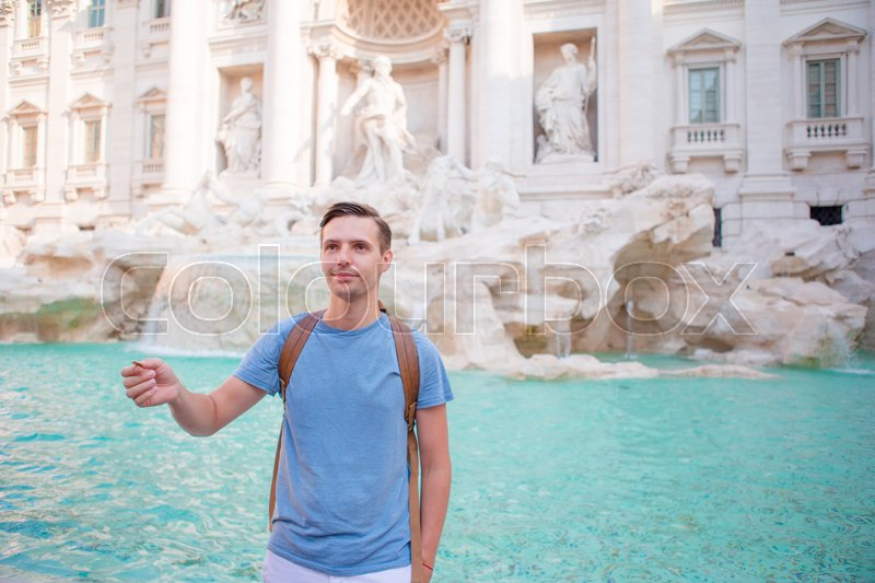 Happy man trowing coins at Trevi Fountain, Rome, Italy for good luck. Caucasian guy making a wish to come back, stock photo