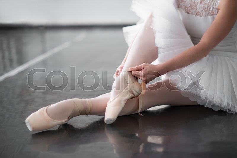 Ballet dancer legs in pointe shoes closeup. Ballerina rehearsal in class, stock photo