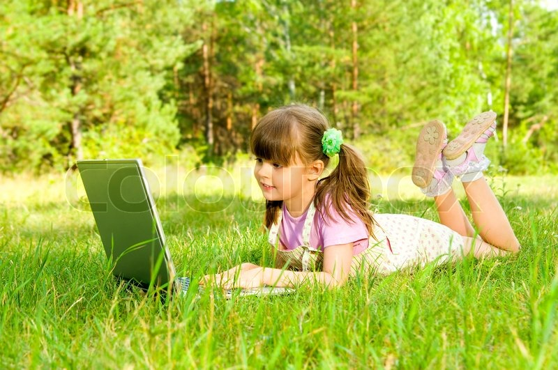 The small nice girl works on a computer, lays on a beautiful green lawn, Smile Profile Adobe RGB (1998), stock photo
