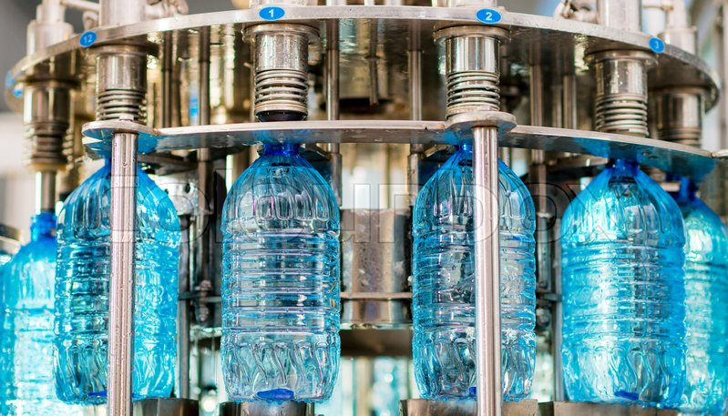 Filling pure bottles with mineral water at a factory, stock photo