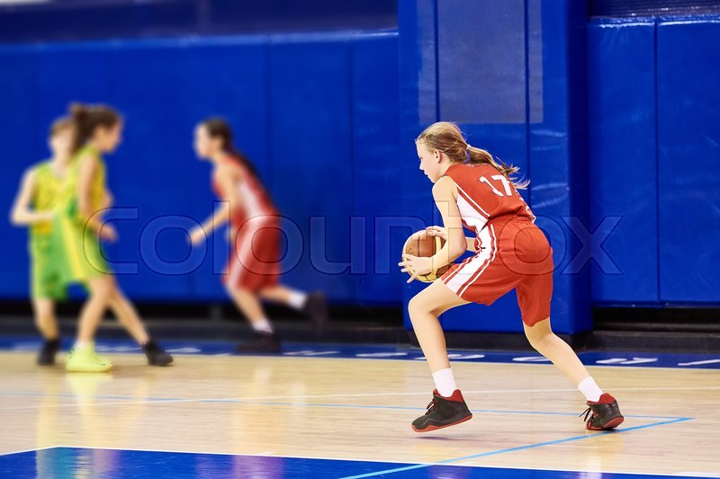 Girls athlete in sport uniform playing basketball indoors, stock photo