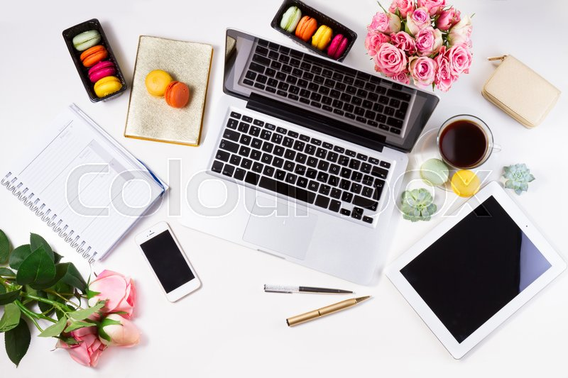 Feminine workspace with laptop, tablet and phone, top view, stock photo
