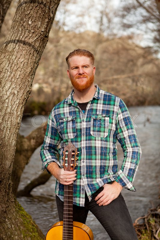 Hipster man with red beard with a guitar in the field, stock photo