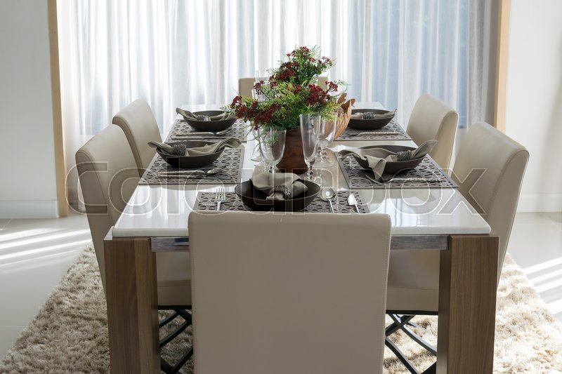 Dining table and comfortable chairs in modern home with elegant table setting, stock photo