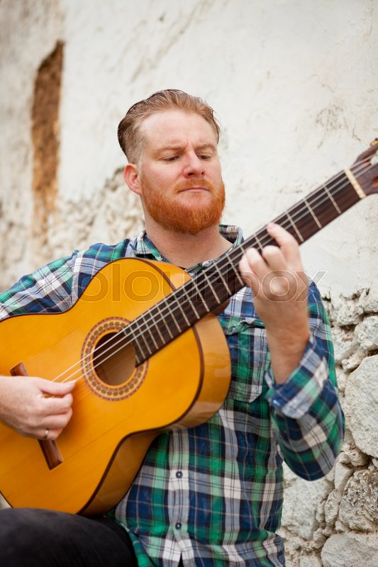 Hipster man with red beard playing a guitar with a old wall of background, stock photo