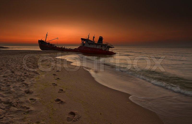 Abandoned broken ship-wreck beached on rocky sea shore. | Stock Photo | Colourbox