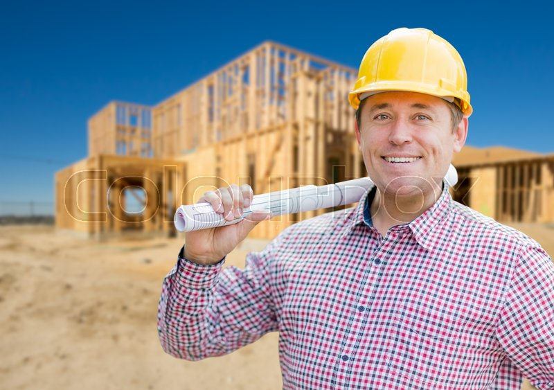 Smiling Contractor Wearing Hardhat Holding Blueprints at Home Construction Site, stock photo