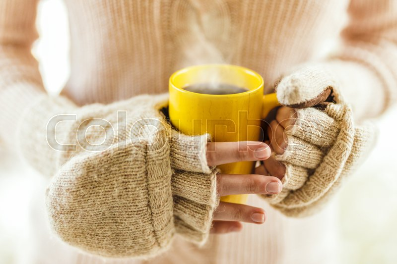 Woman holding hot steaming coffee cup close up photo, stock photo