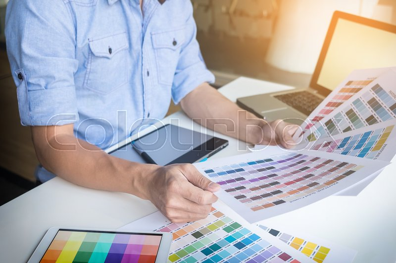 Young graphic designer working on a desktop computer and using some color swatches, stock photo
