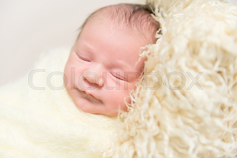 Sweet hairy baby sleeping on a furry yellow pillow, wrapped up with a blanket, closeup, stock photo