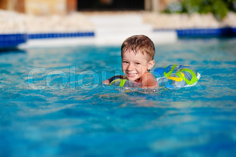 Happy Little Boy Playing With Colorful Inflatable Ring In