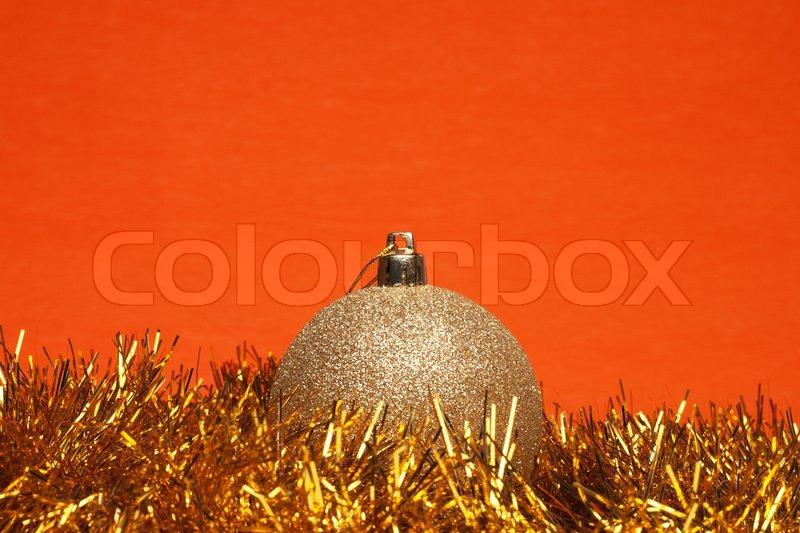 gl nzende weihnachtskugel mit lametta ber orange hintergrund stockfoto colourbox. Black Bedroom Furniture Sets. Home Design Ideas