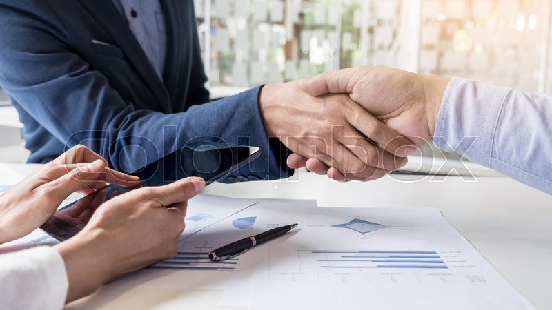Business handshake of two men demonstrating their agreement to sign agreement or contract between their firms, companies, enterprises, stock photo