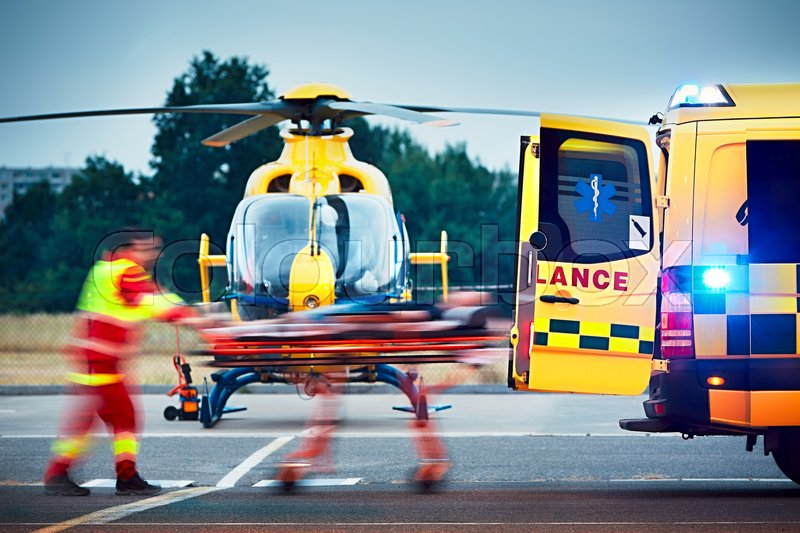 Cooperation between air rescue service and emergency medical service on the ground. Paramedic is pulling stretcher with patient to the ambulance car, stock photo