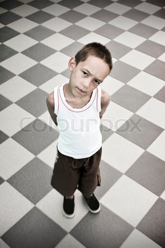 sad boy standing alone over black and white background stock photo