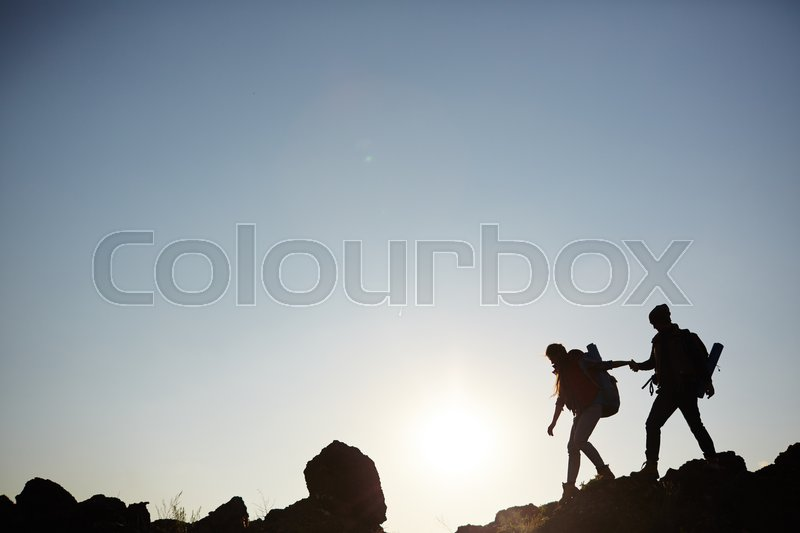 Backlit dark silhouettes of couple hiking in mountains, young man following girlfriends holding hands, side view graphic image, stock photo