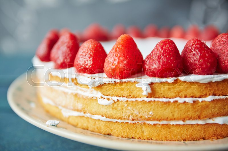 Closeup shot of simple creamy naked cake decorated with fresh ripe strawberries and white icing, stock photo