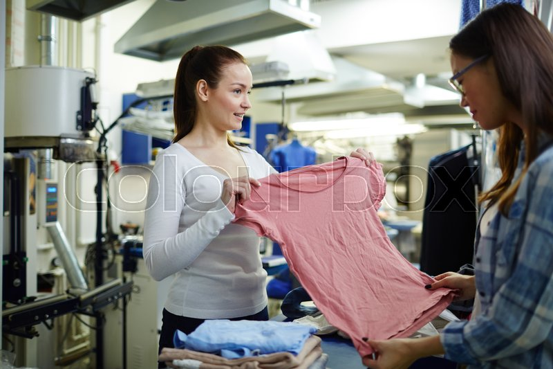Owner of clothing store showing her client pink T-shirt, stock photo