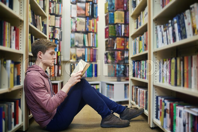 Serious guy sitting on the floor between bookshelves and reading in library, stock photo