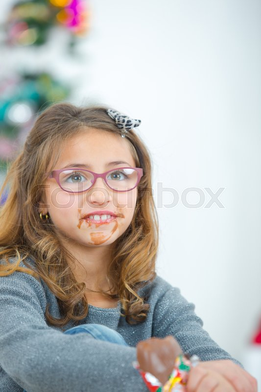 Girl eating chocolate, mouth in a mess, stock photo