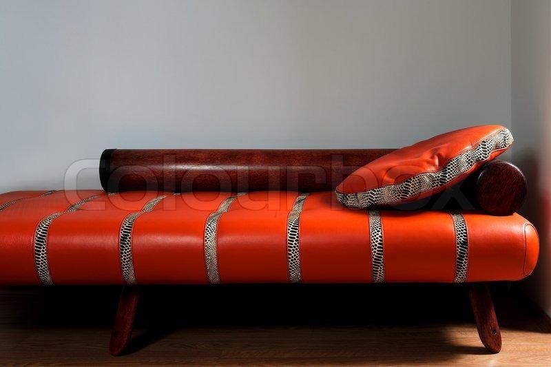 leder rotes sofa auf einem hintergrund von einer wand. Black Bedroom Furniture Sets. Home Design Ideas
