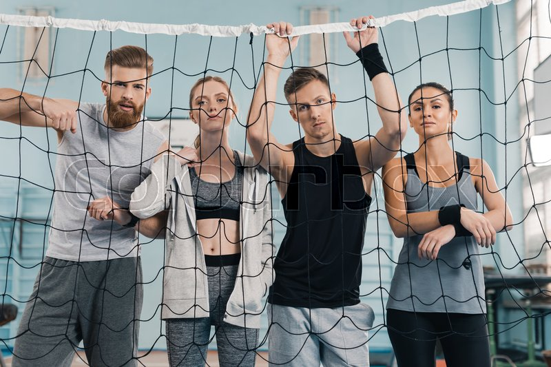 Sporty young people looking at camera through net in sports hall , stock photo