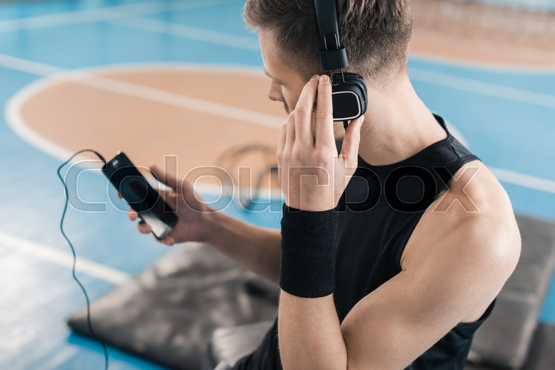 Young sportsman in headphones using smartphone in sports center, stock photo