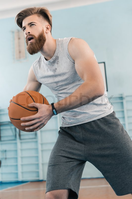 Bearded young athletic man playing basketball in sports center, stock photo