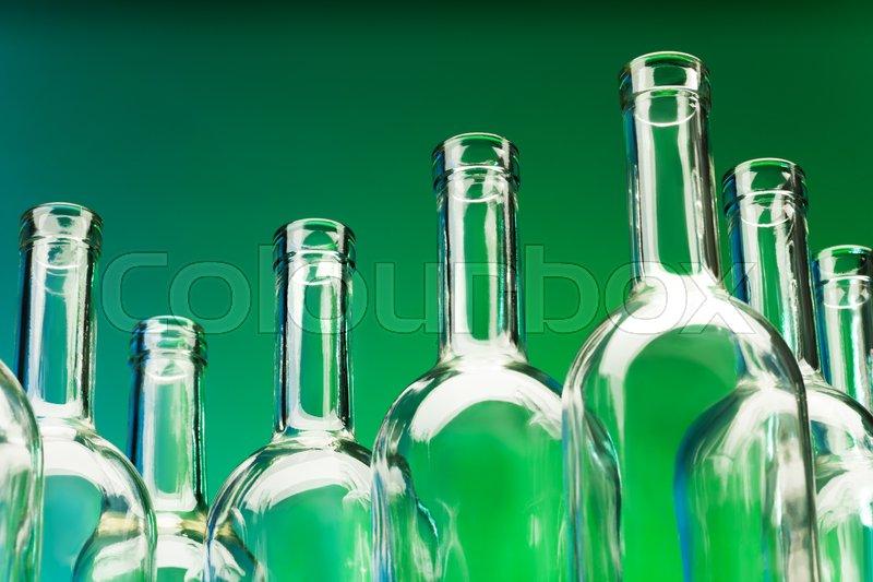 Picture of seven empty wine bottles\' bottlenecks against a green background, stock photo