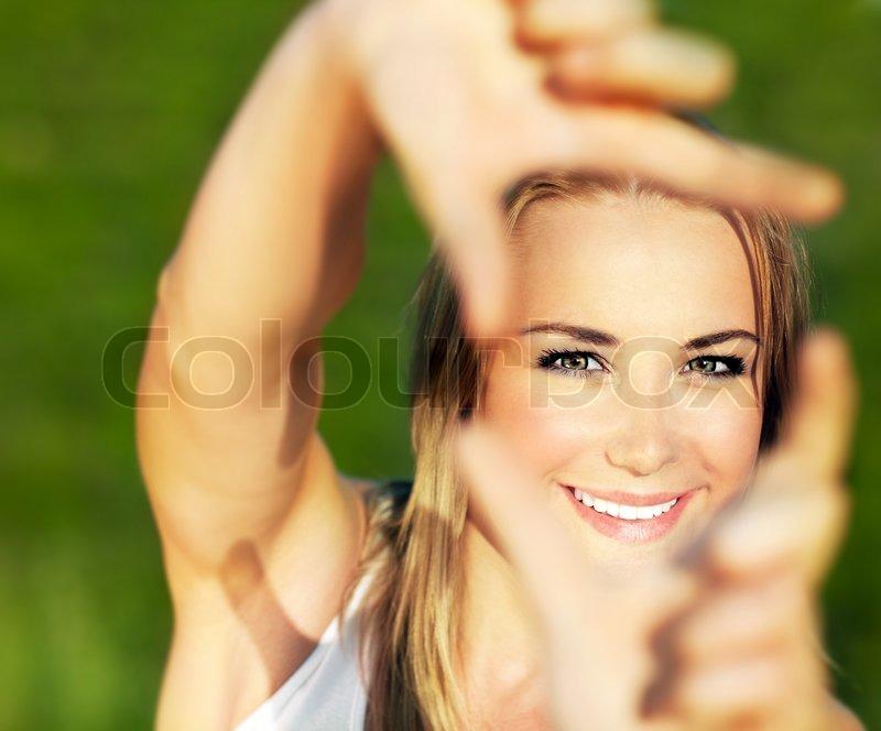 Hübsche Mädchen Spaß im Freien , so dass Rahmen mit den Händen ...