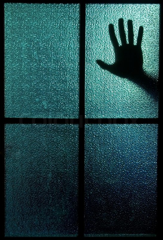 Silhouette Of A Hand Behind A Window Or Glass Door Symbolizing